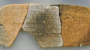 A sample of Linear B script, the earliest Greek writing, 1450 BC, and an adaptation of the earlier Minoan Linear A script. This piece contains information on the distribution of bovine, pig and deer hides to shoe and saddle-makers. It is a script made up of 90 syllabic signs, ideograms and numbers, a form earlier than that used for the Homeric poems. These clay tablets were fortuitously preserved when they were baked in the Mycenaean palace of Pylos fire 250 years later.